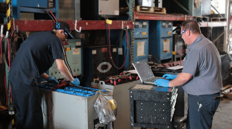 Employees working on forklift battery at DC Power Solutions.
