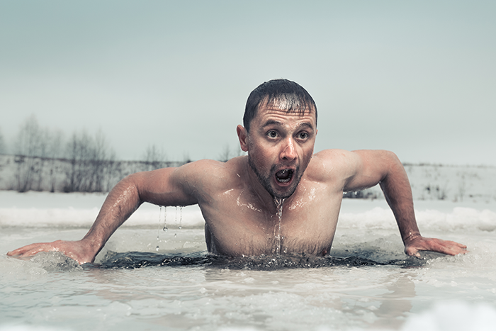 Man climbing out of frozen river